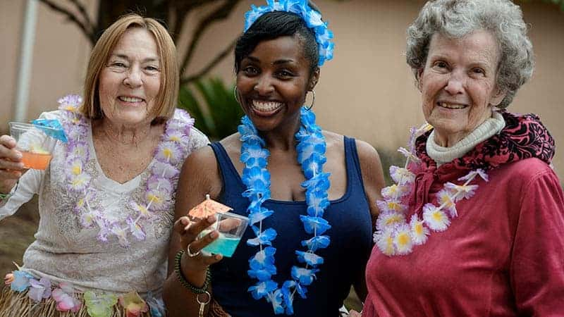 Staff member with 2 senior women holding drinks at Hawaiian themed social event at Sunflower Springs Homosassa assisted living community